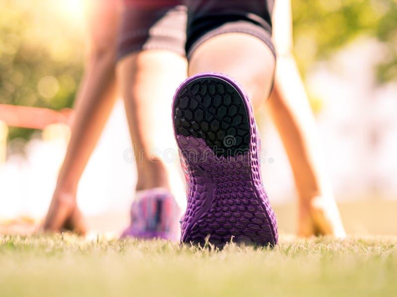 Constantes prontos vão Close up dos tênis de corrida na grama, na jovem senhora na posição de começo e em ir correr no parque foto de stock