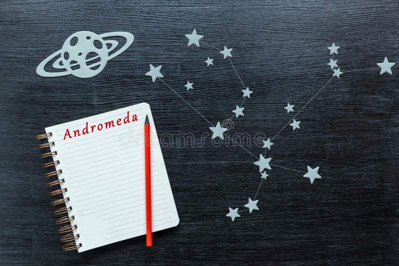 Constellations Andromeda. Zodiacal star, constellations Andromeda on a black background with a notepad and pencil royalty free stock photos