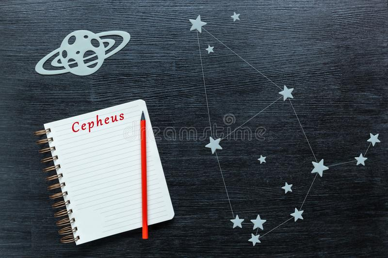 Constellations Cepheus. Zodiacal star, constellations Cepheus on a black background with a notepad and pencil royalty free stock photo
