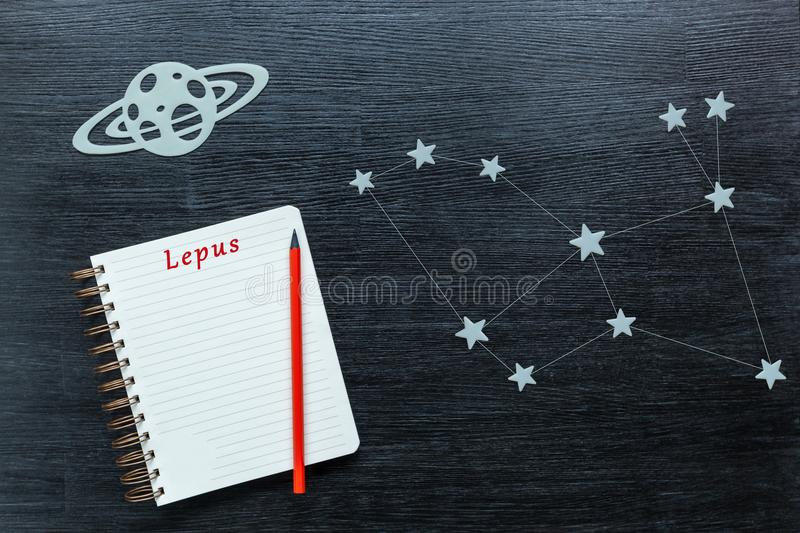 Constellations Lepus. Zodiacal star, constellations Lepus on a black background with a notepad and pencil royalty free stock image