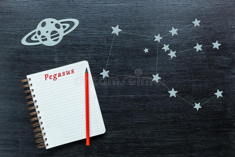 Constellations Pegasus. Zodiacal star, constellations Pegasus on a black background with a notepad and pencil stock image