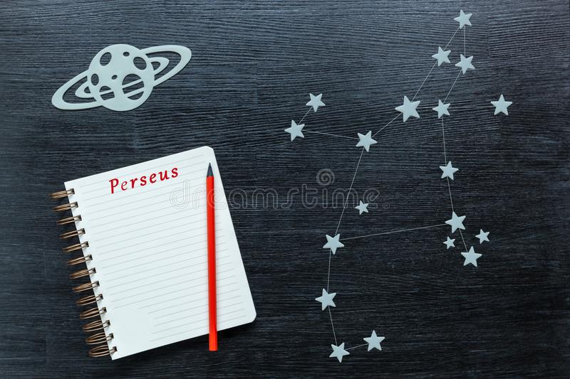 Constellations Perseus. Zodiacal star, constellations Perseus on a black background with a notepad and pencil royalty free stock images