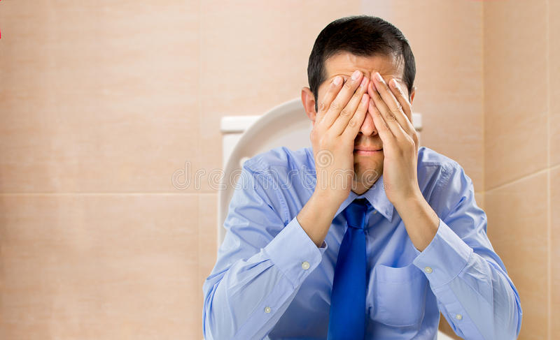 Constipated man. Businessman in the toilet with problems of constipation stock images