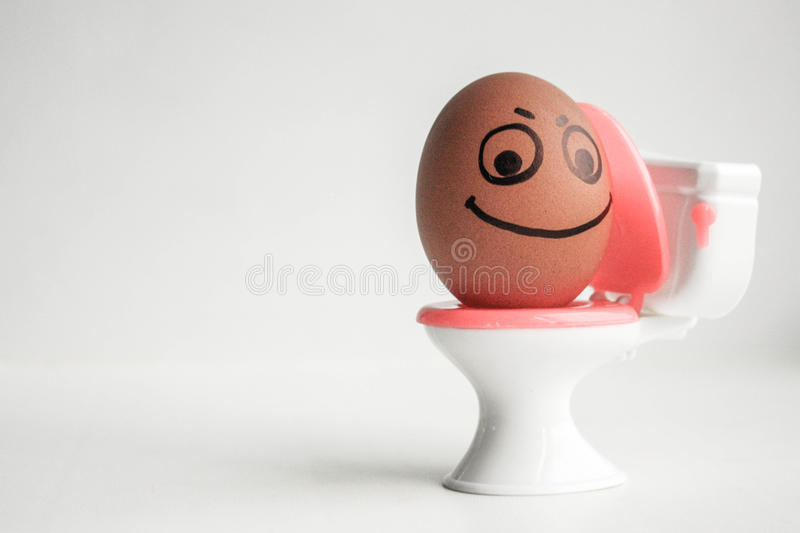 Constipation concept. A funny egg. With a painted face on the toilet seat sits tuzhitsya. Photo for your design royalty free stock photo