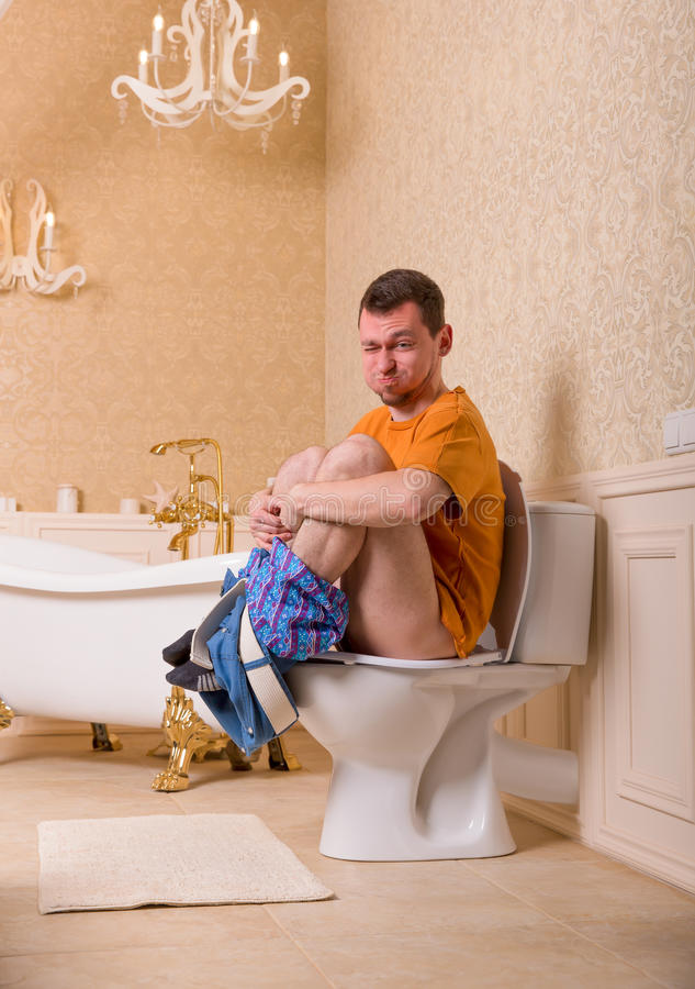 Constipation problem, man sitting on toilet bowl. Constipation problem concept. Man with pants down sitting on the toilet bowl stock photo