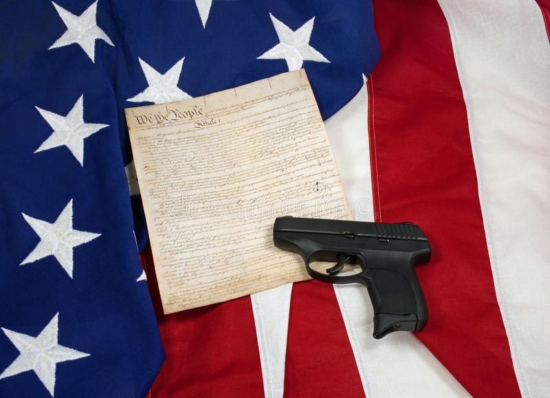 Constitution with Hand Gun on American Flag. Concept of Second Amendment rights royalty free stock photo