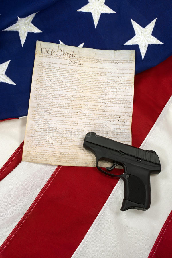 Constitution with Hand Gun on American Flag, Vertical. Copy of US Constitution with hand gun on American flag background. Concept of second amendment rights stock photo