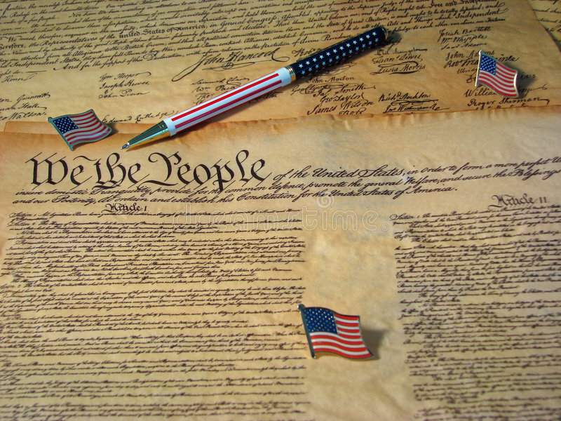 Constitution Pen and Flags. A copy of the Constitution of the United States resting on a copy of the Declaration of Independence accompanied by flags and a flag royalty free stock photos