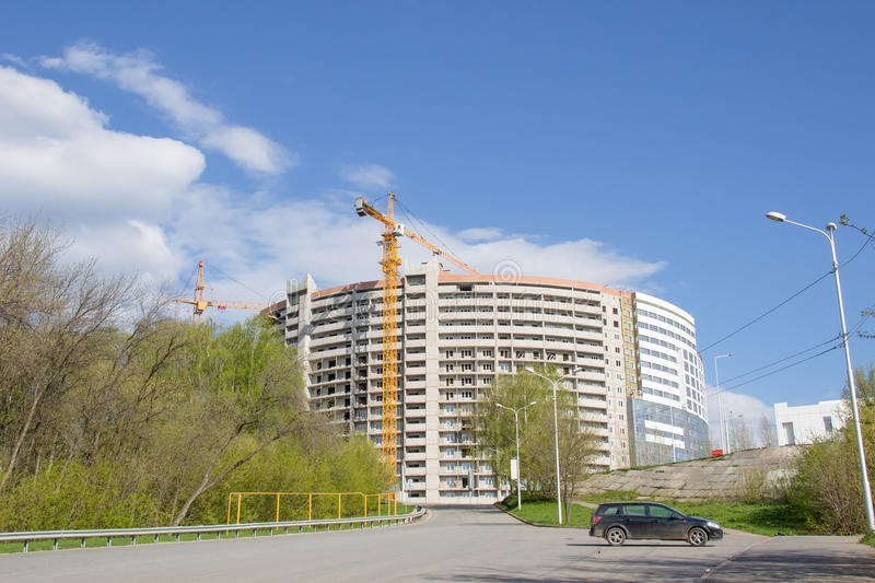 Constraction site. Unfinished concrete building. Black car on road stock images