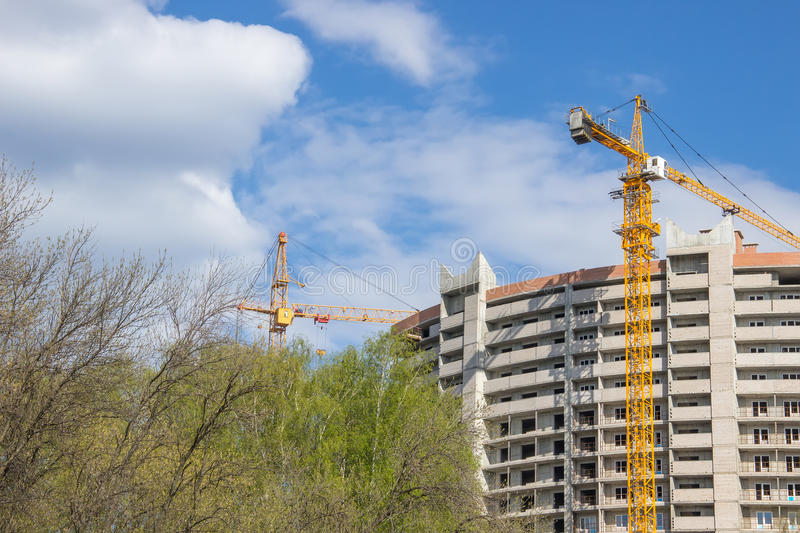 Constraction site. Unfinished concrete house and two building cranes on one side stock images