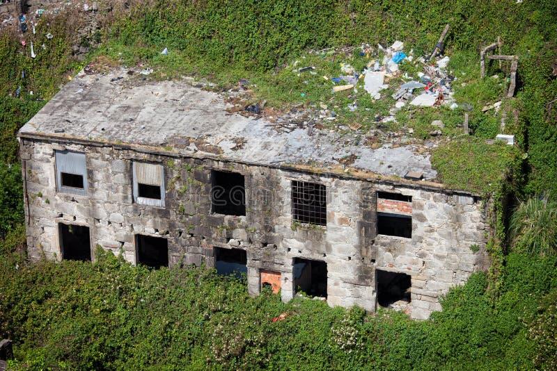 Construção abandonada cercada plantas fotos de stock royalty free