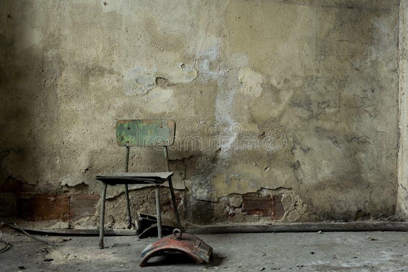 Construção abandonada velha da fábrica, cadeira de madeira velha imagem de stock