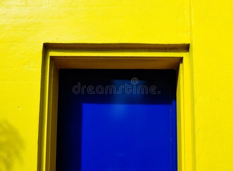 Construção amarela brilhante com porta azul fotografia de stock