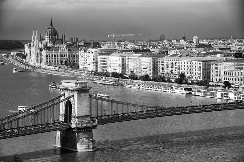 A construção bonita do parlamento húngaro e da ponte Chain sob nuvens de tempestade Budapest imagem de stock