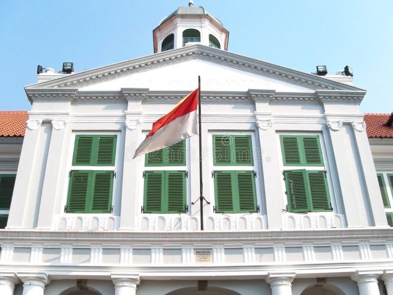 Construção branca com a bandeira de Indonésia na frente dela fotografia de stock royalty free