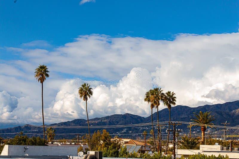 Construção, casas e montanhês de Glendale conduzindo às montanhas de San Gabriel, com céu azul e as nuvens elevando-se fotografia de stock