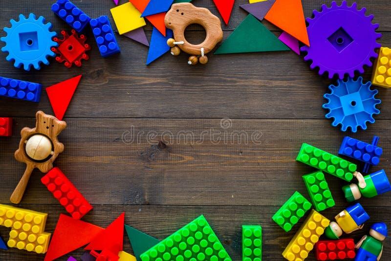 A construção colorida brinca para o quadro das crianças no espaço de madeira escuro da cópia da opinião superior do fundo foto de stock royalty free