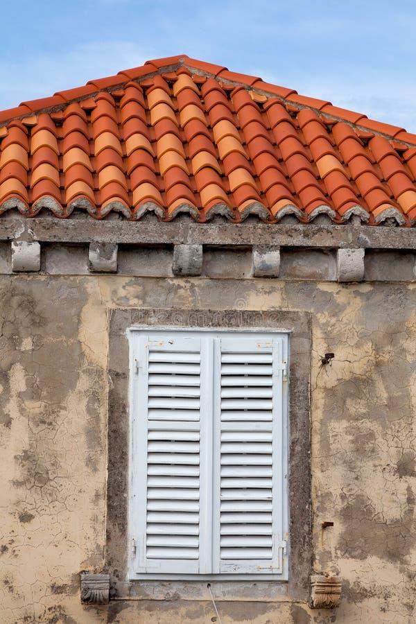 A construção com as telhas de telhado alaranjadas e wodden a janela shuttered fotografia de stock