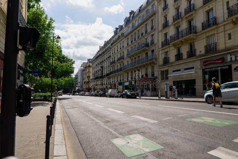 Construção com grandes janelas e balcões com as flores em Paris contra um céu nebuloso Vista inferior imagens de stock royalty free