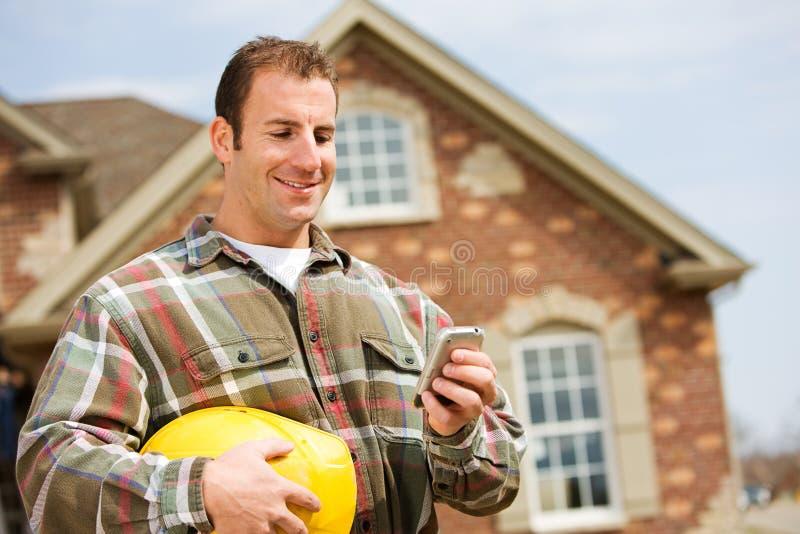 Construção: Construtor Using Cell Phone imagens de stock
