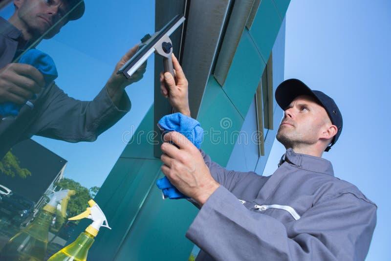 Construção da janela da limpeza do homem fora imagem de stock