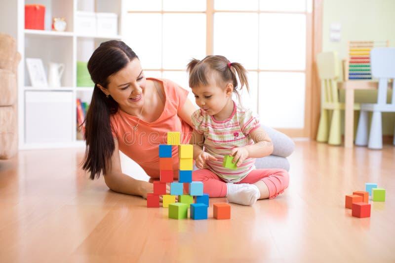Construção da mãe e da criança dos blocos do brinquedo em casa Conceito de família imagem de stock