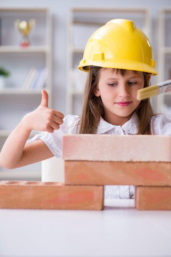 A construção da moça com tijolos da construção imagem de stock