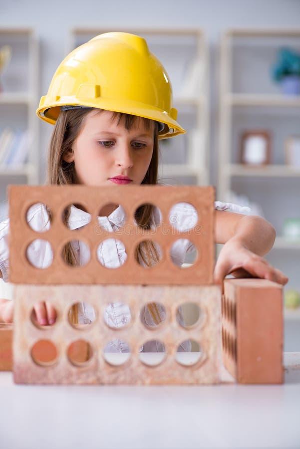 A construção da moça com tijolos da construção fotos de stock royalty free