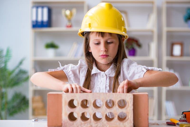 A construção da moça com tijolos da construção imagem de stock royalty free