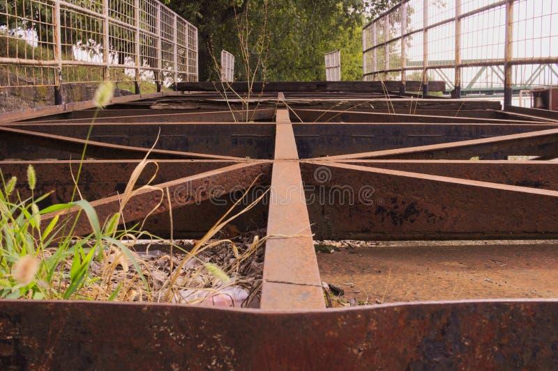 Construção de aço velha oxidada que encontra-se na terra imagens de stock