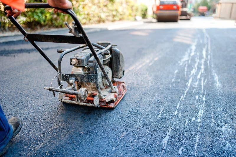 Construção de estradas com o trabalhador que pavimenta o betume ou o asfalto fresco foto de stock royalty free