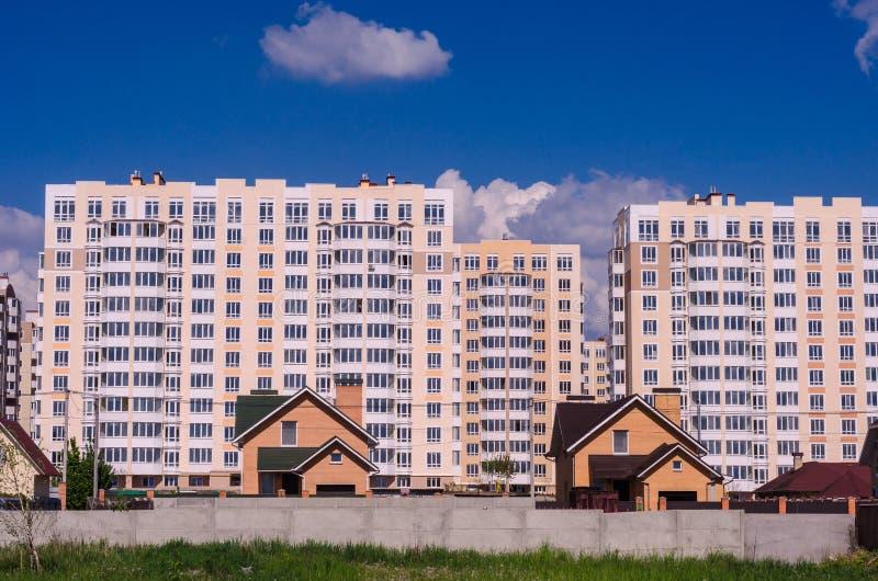A construção de grandes prédios de apartamentos desloca pequeno ho imagem de stock