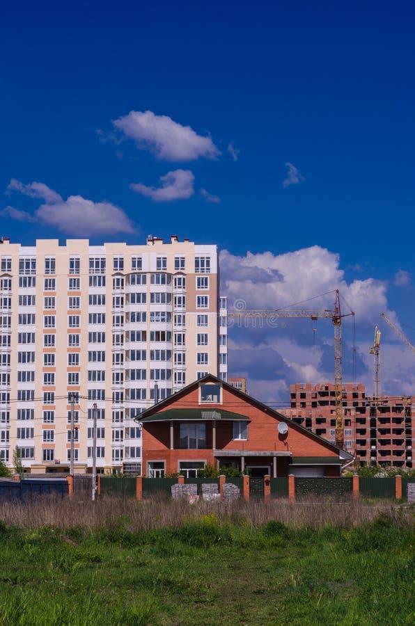 A construção de grandes prédios de apartamentos desloca pequeno ho fotografia de stock royalty free