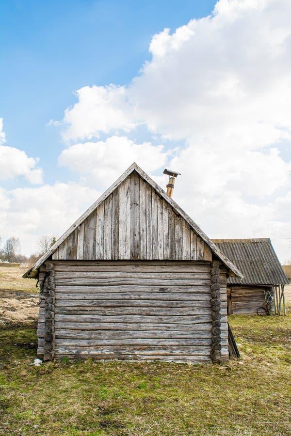 Construção de madeira abandonada danificada velha, casa de campo quebrada de logs de madeira, fundo slavic histórico da abstração imagens de stock