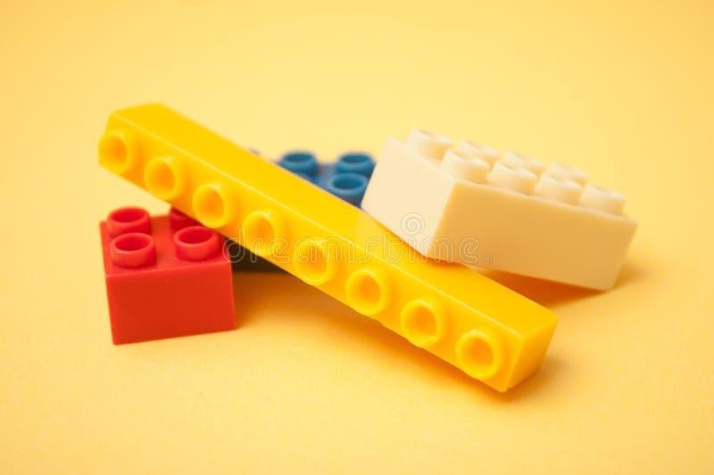 Construção de tijolos plástica colorida no fundo amarelo fotografia de stock