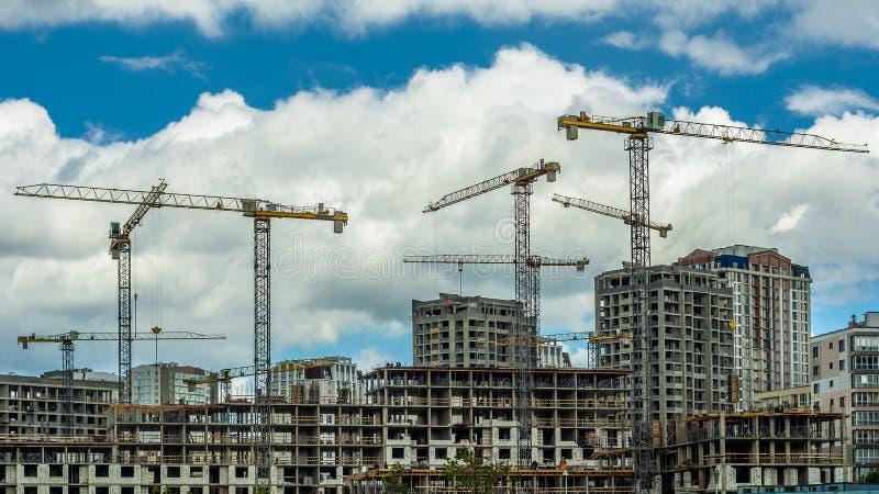 construção de um bloco de cidade residencial novo com o guindaste liftable contra o céu nebuloso azul foto de stock