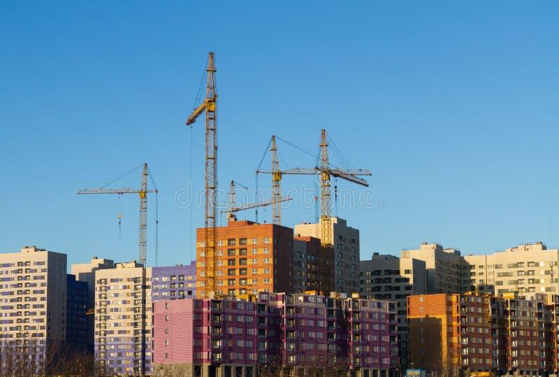 A construção de um distrito residencial de casas do multi-andar com elevação de guindastes da cor amarela em um fundo do céu azul fotos de stock