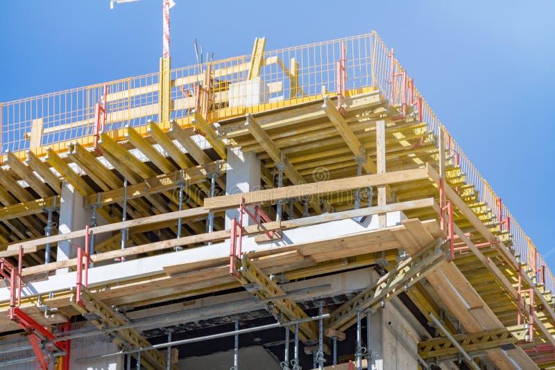 Construção de uma casa, ferramentas para a construção, uma casa concreta do multi-andar monolítico, apoios para um fechamento de  fotos de stock