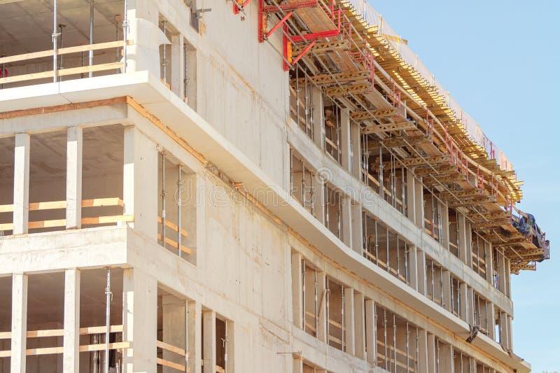Construção de uma casa, ferramentas para a construção, uma casa concreta do multi-andar monolítico, apoios para um fechamento de  imagem de stock royalty free