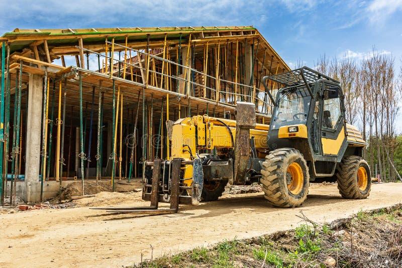 Construção de uma casa unifamiliar Construindo a estrutura externo com um elevador da carga fotos de stock royalty free
