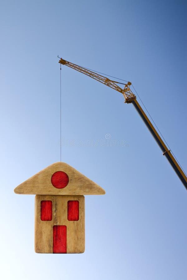 A construção de uma construção pré-fabricada de madeira - imagem do conceito com um guindaste de torre que guarda uma casa de mad imagens de stock royalty free