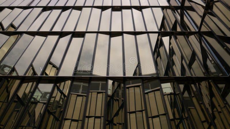 Construção de vidro com lotes das janelas O c?u ? refletido nas janelas fotos de stock