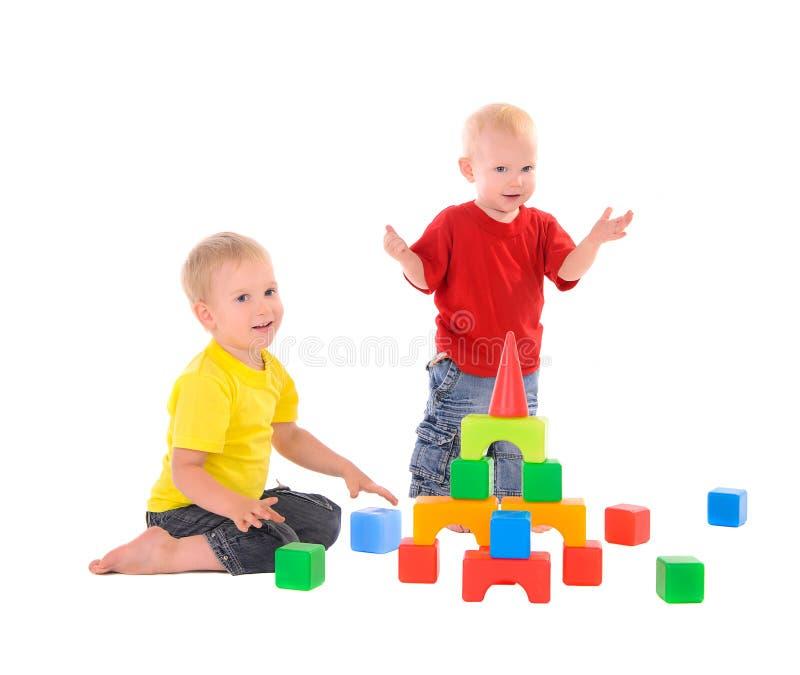 Construção do brinquedo de duas construções dos irmãos de cubos coloridos fotos de stock