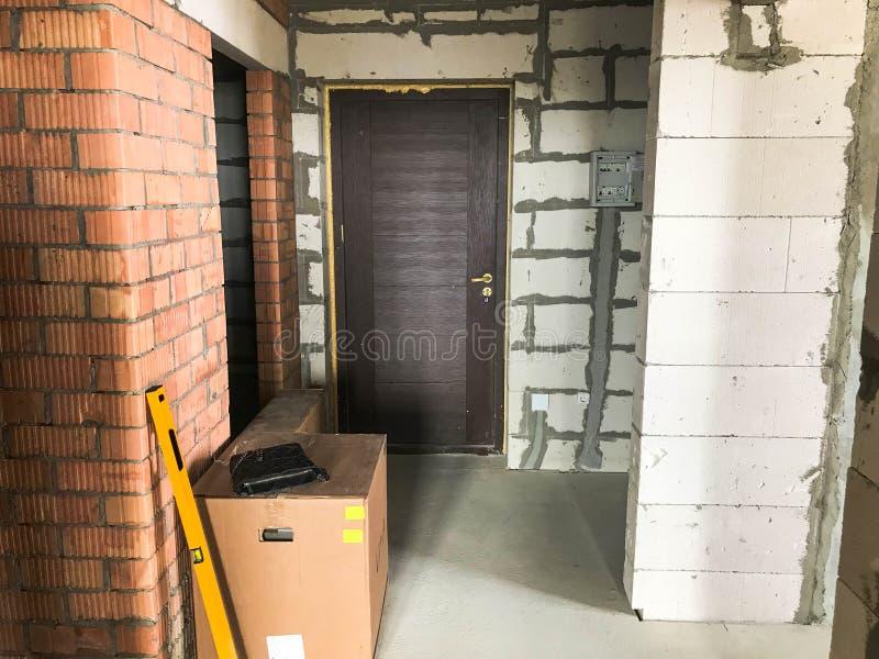 Construção do reparo em uma construção nova com um plano livre, em um apartamento sem reparo com as paredes do silicato do tijolo fotos de stock