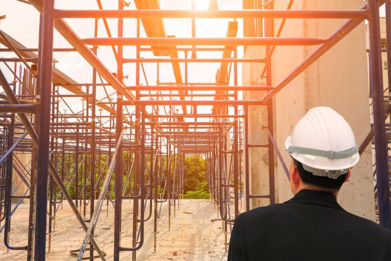 construção do trabalho da verificação do Arquiteto-coordenador em um terreno de construção com manhã da luz do nascer do sol fotografia de stock