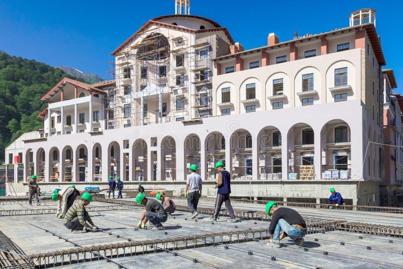 Construção dos hotéis na estância de esqui da montanha de Sochi para os Olympics 2014 Trabalho dos construtores no canteiro de ob fotografia de stock royalty free