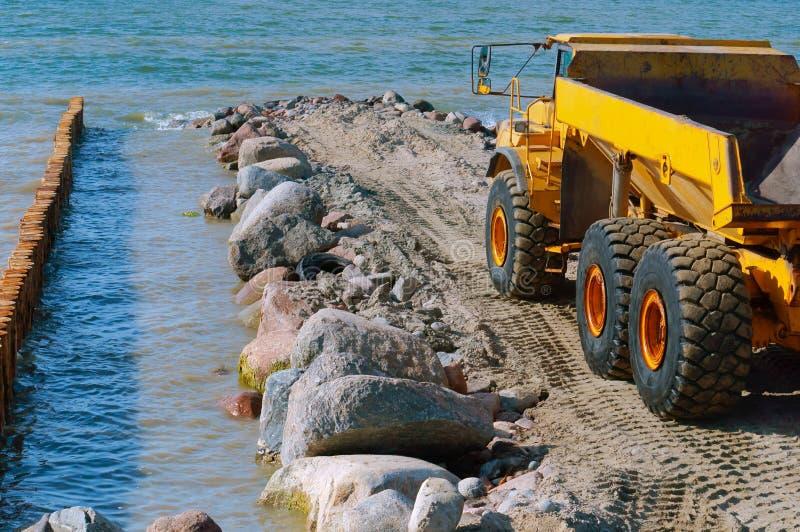 Construção dos quebra-mares, equipamento de construção na costa de mar fotos de stock