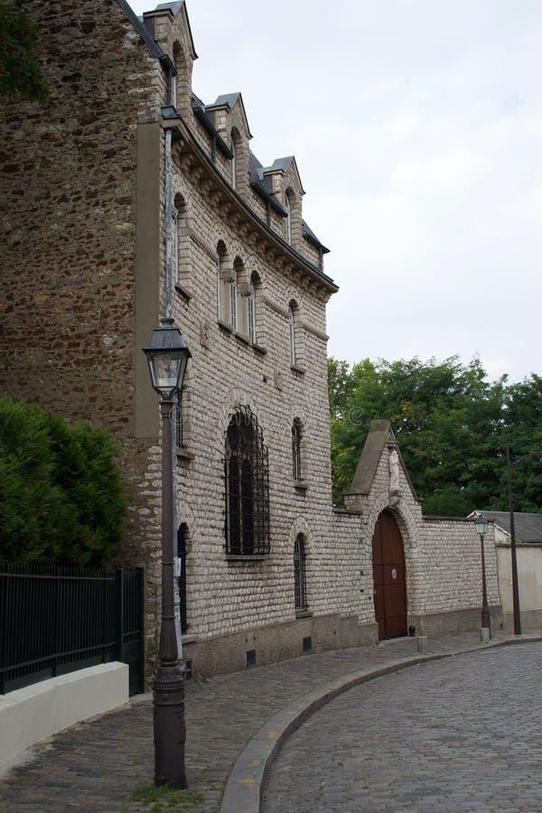Constru??o e lamposts franceses hist?ricos em uma rua cobbled em Montmart Paris, Fran imagem de stock