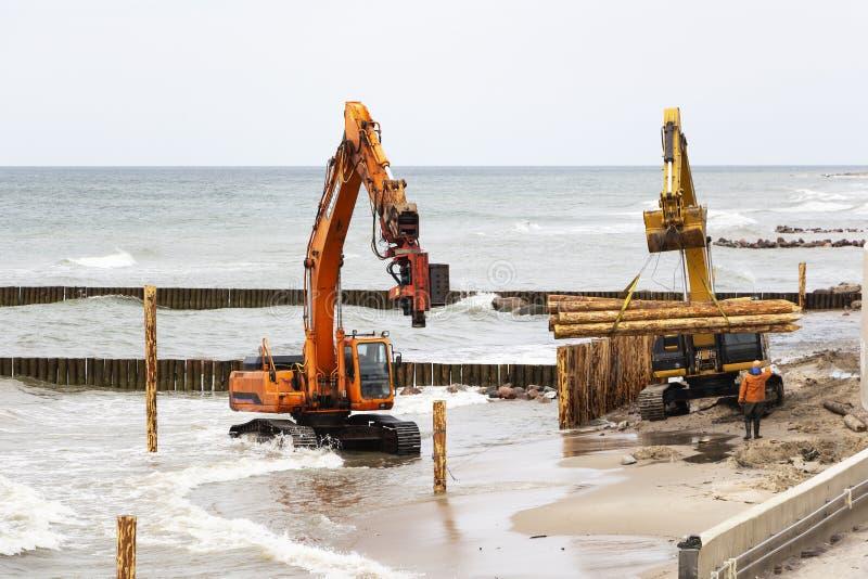 Construção e reforço da costa, equipamento de construção na costa de mar fotos de stock