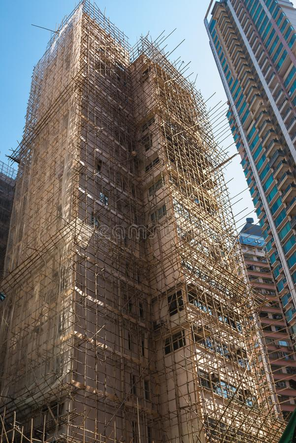 A construção em Hong Kong está sob a reconstrução, cercada pelo andaime do bambu Arquitetura, tema da construção foto de stock